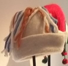 A white felted hat with a turned up brim.  the shape reminds me of an upturned flower pot. The top of the hat has felted woollen tassels.