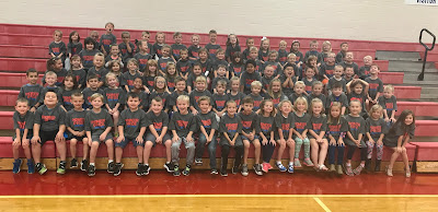 The class of 2030 students sitting on the gym bleachers for Class photo.