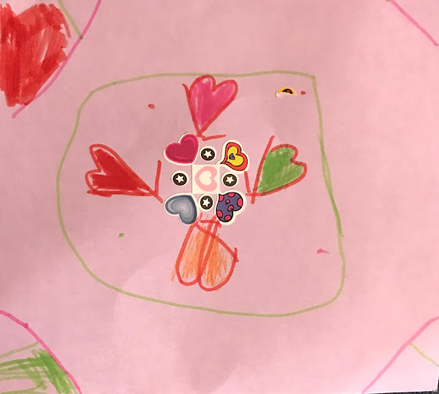 A pink piece of paper with felt tip hearts, stickers and other patterns