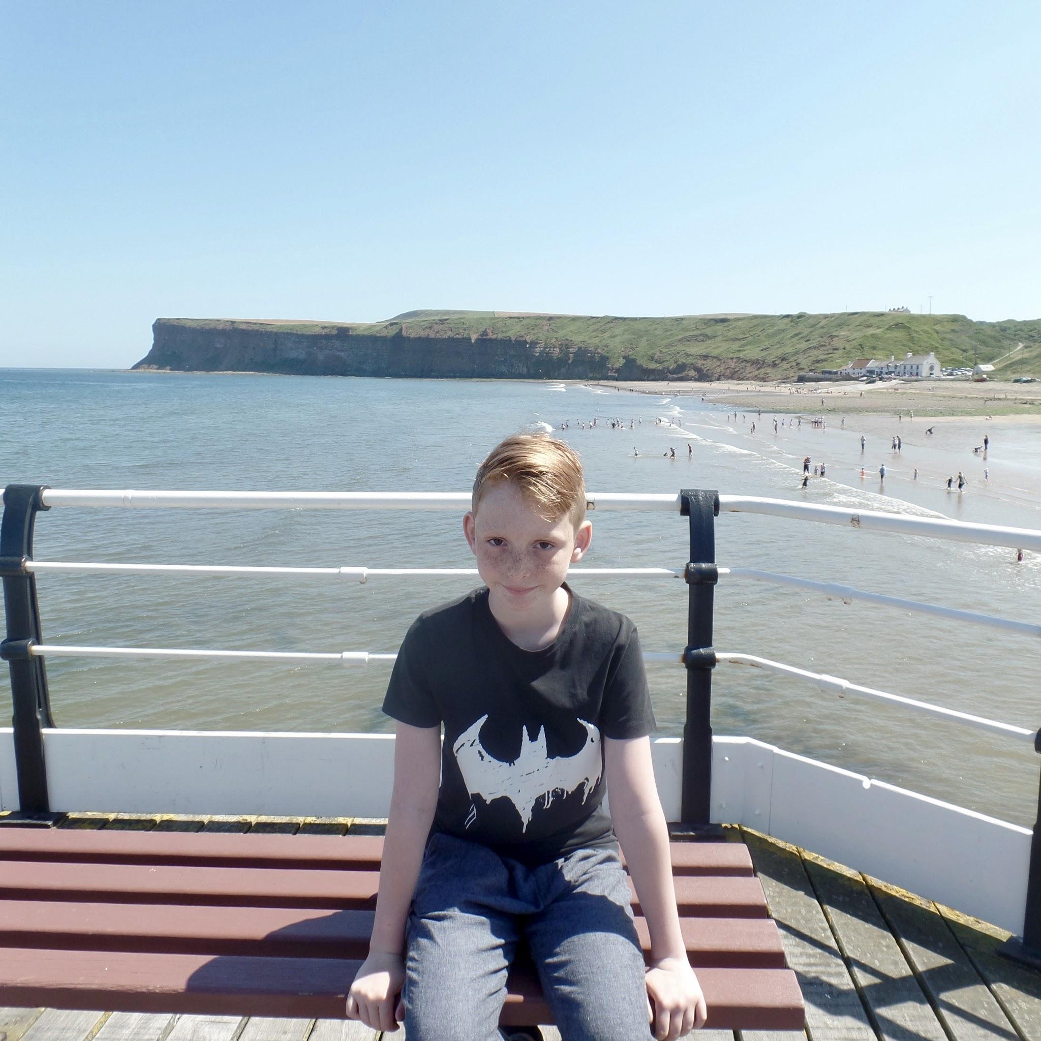 Boy sat on pier