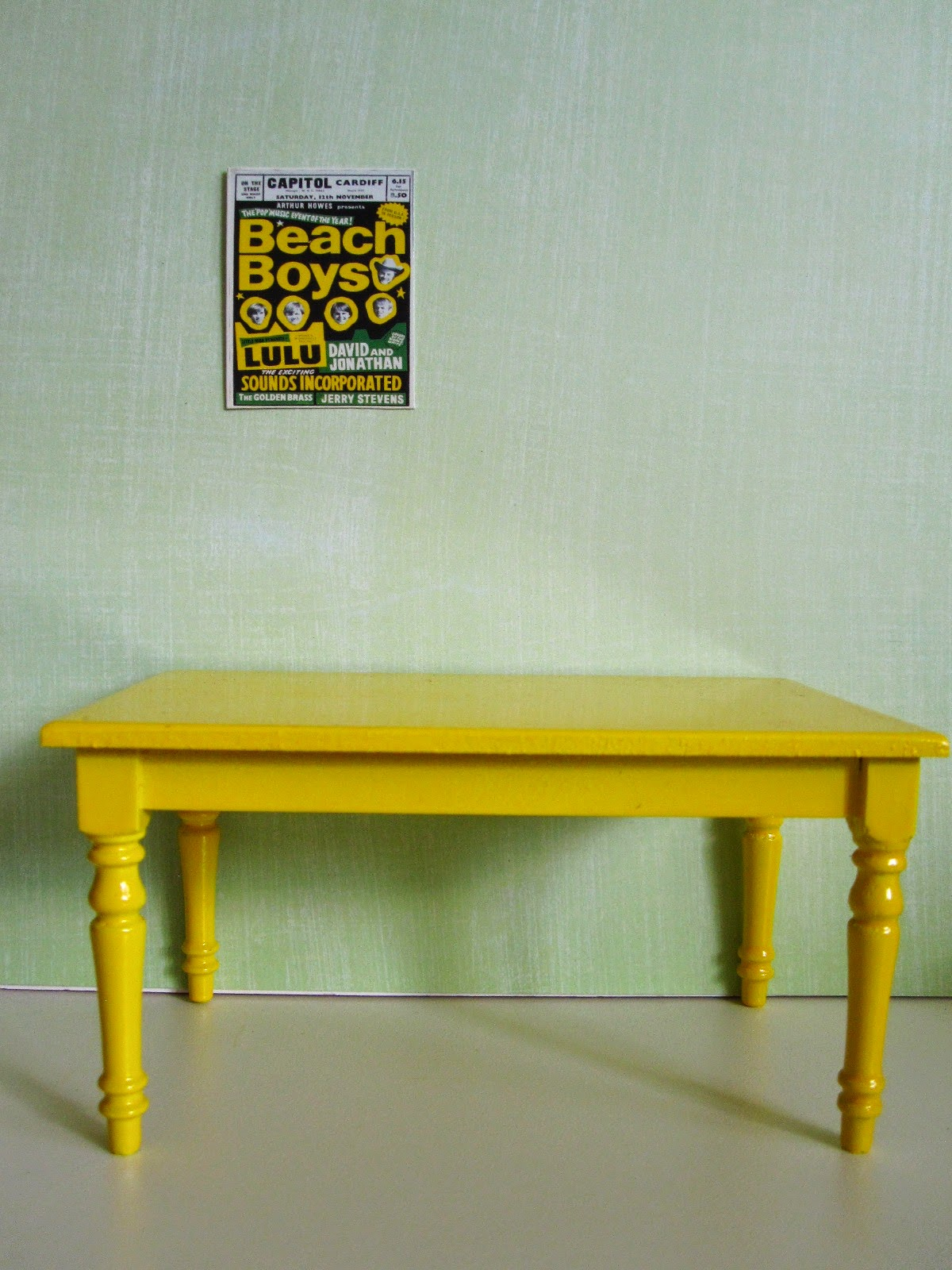Bright 1960s Beach Boys poster on a green wall with a modern dolls' house miniature yellow table underneath,