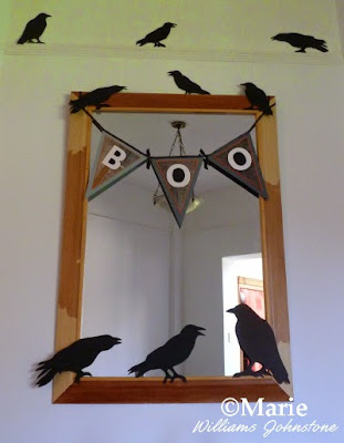 A small handmade banner or garland decorates a mirror for Halloween