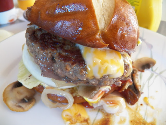 Burger with Pretzel Bun, mushrooms, onions and cheese