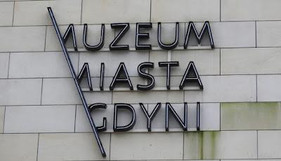 Muzeum Miasta Gdyni - logo wiszące na fasadzie budynku, pierwsze litery trzech słów wyłaniają się ze skośnej lini łączącej napis.