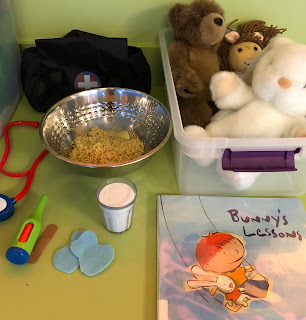 tactile items include bunny puppet, doll, toy stethoscope, toy thermometer, toy glass of milk, blue flannel splotches, bowl of noodles, book