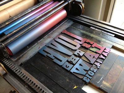 Bed of a metal letterpress with type set up that reads Love is the Law
