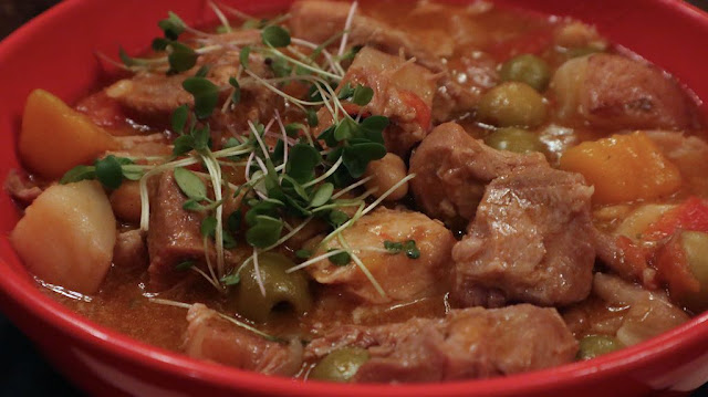 Puerto rican-style pork stew in a red bowl