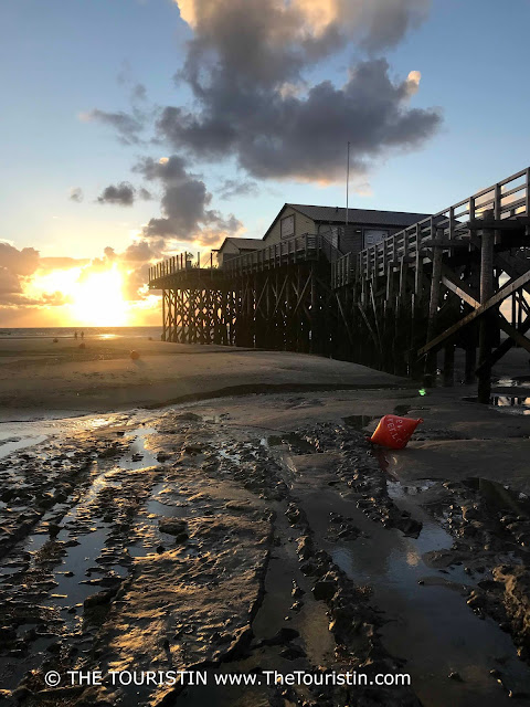A wooden stilt cottage and its wooden pier during low tide at sunset.