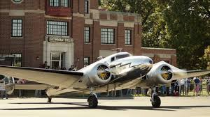 bowman field historic main building in the background with a world war II plane in front of the building