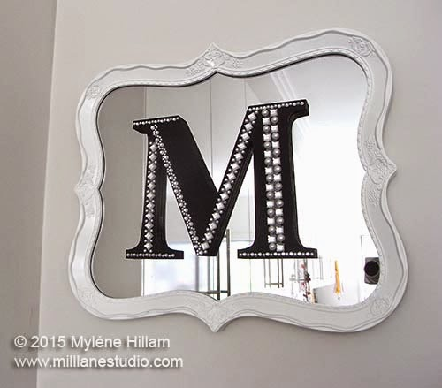 "White resin framed mirror with black monogrammed letter ""M"" on the mirror, decorated with crystal and pearl borders."