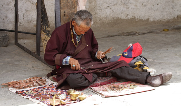 Local Ladakhi man selling incense stick and trinkets at Shey Palace, Ladakh, India
