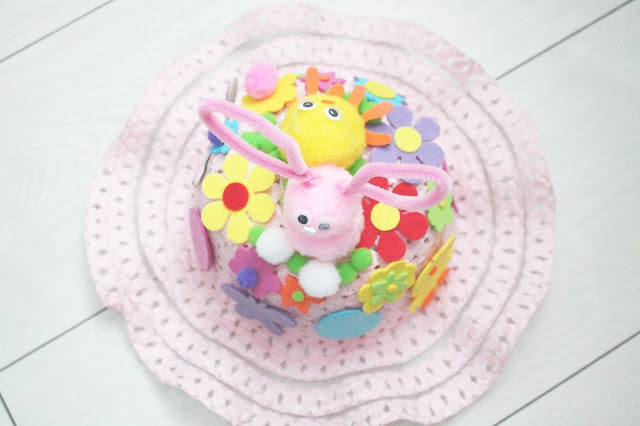 pink Easter bonnet with bunny and chic sitting on top in bed of flowers and grass