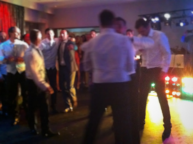 A blurred photo of a group of men dancing at a wedding with disco lights in the background