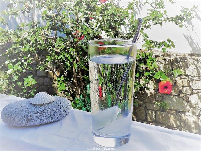 szklanka z wodą i białą masą na łyżce, grecki deser w szklance na tle hibiskusa