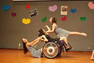 Κοπέλα σε αμαξίδιο κάνει φιγούρες με δύο χορεύτριες συνοδούς