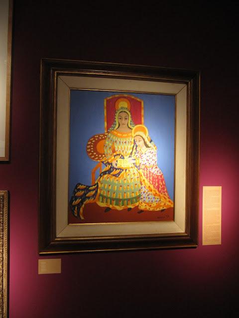 Imagem religiosa, mostra uma mulher sentada de frente para o observador acompanhada de uma moça que está de pé. As duas usam vestidos longos e coloridos.