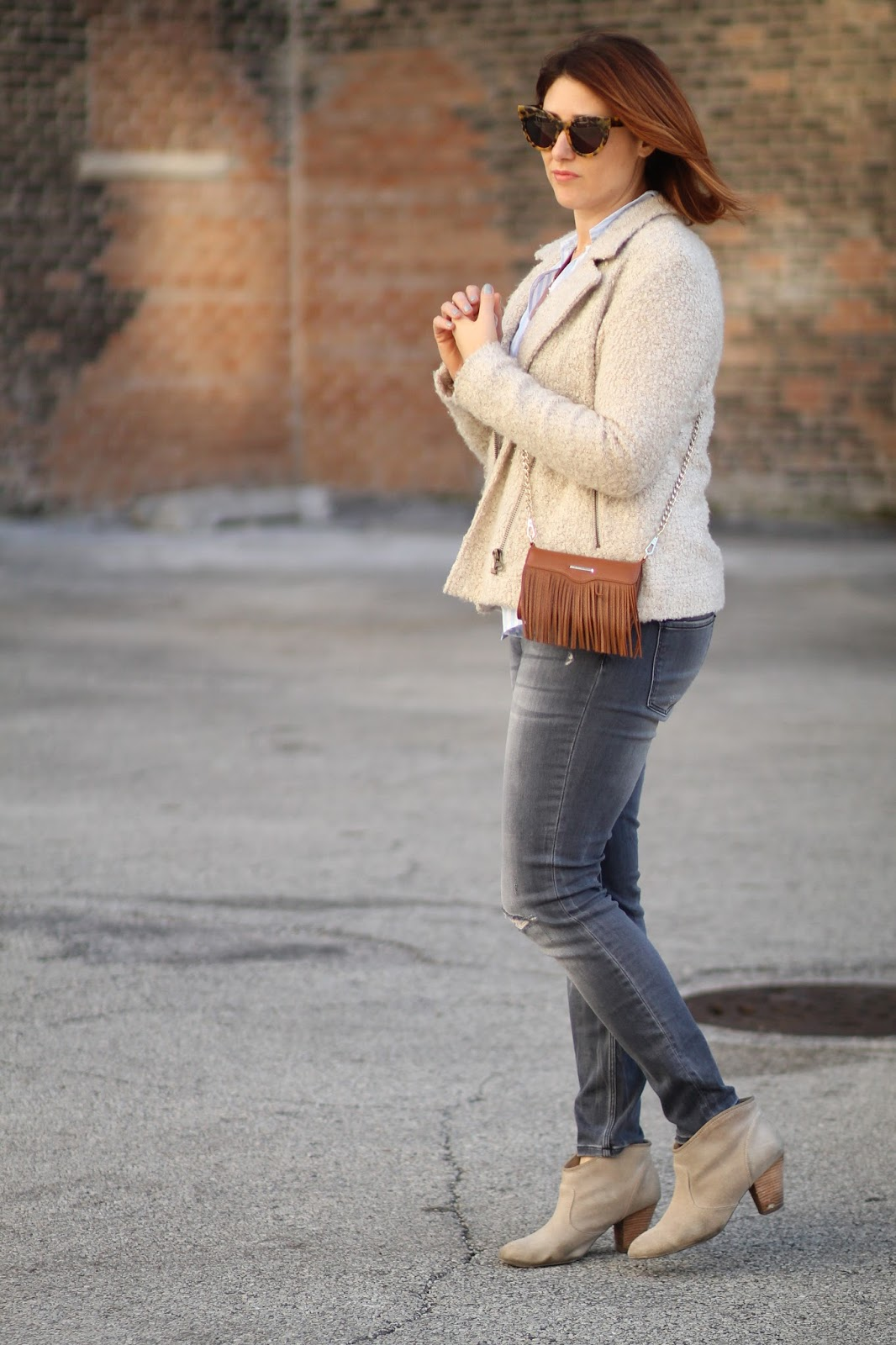 casual outfit idea, brunch look, weekend outfit, button down shirt, moto jacket, fringe bag purse, suede booties and distressed ripped gray jeans, Rebecca Minkoff fringe phone case, karen walker sunglasses, sunburst