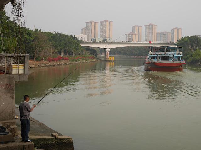 man fishing as a ship travels down the Jiangmen Waterway