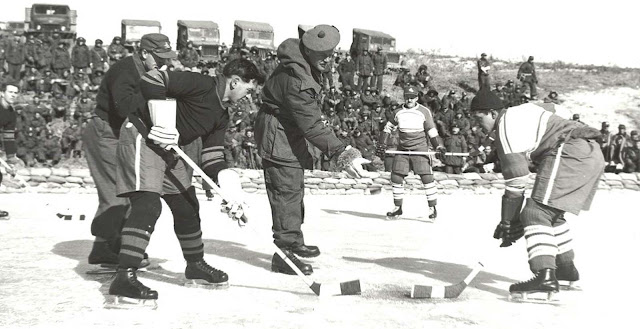 "Brigadier John Rockingham drops the puck for a match between 1st Battalion, Princess Patricia's Canadian Light Infantry (left) and 2nd Battalion, Royal 22e Regiment ""Vandoos"" (right) during the Korean War. Playing for the Patricias was Private W. Wolfe. For the Royal 22e Regiment, Private R. Halley."