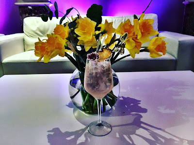 Cocktail in front of a bunch of daffodils