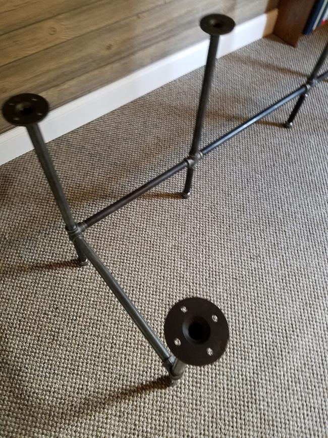 pipe desk base on carpeted floor.
