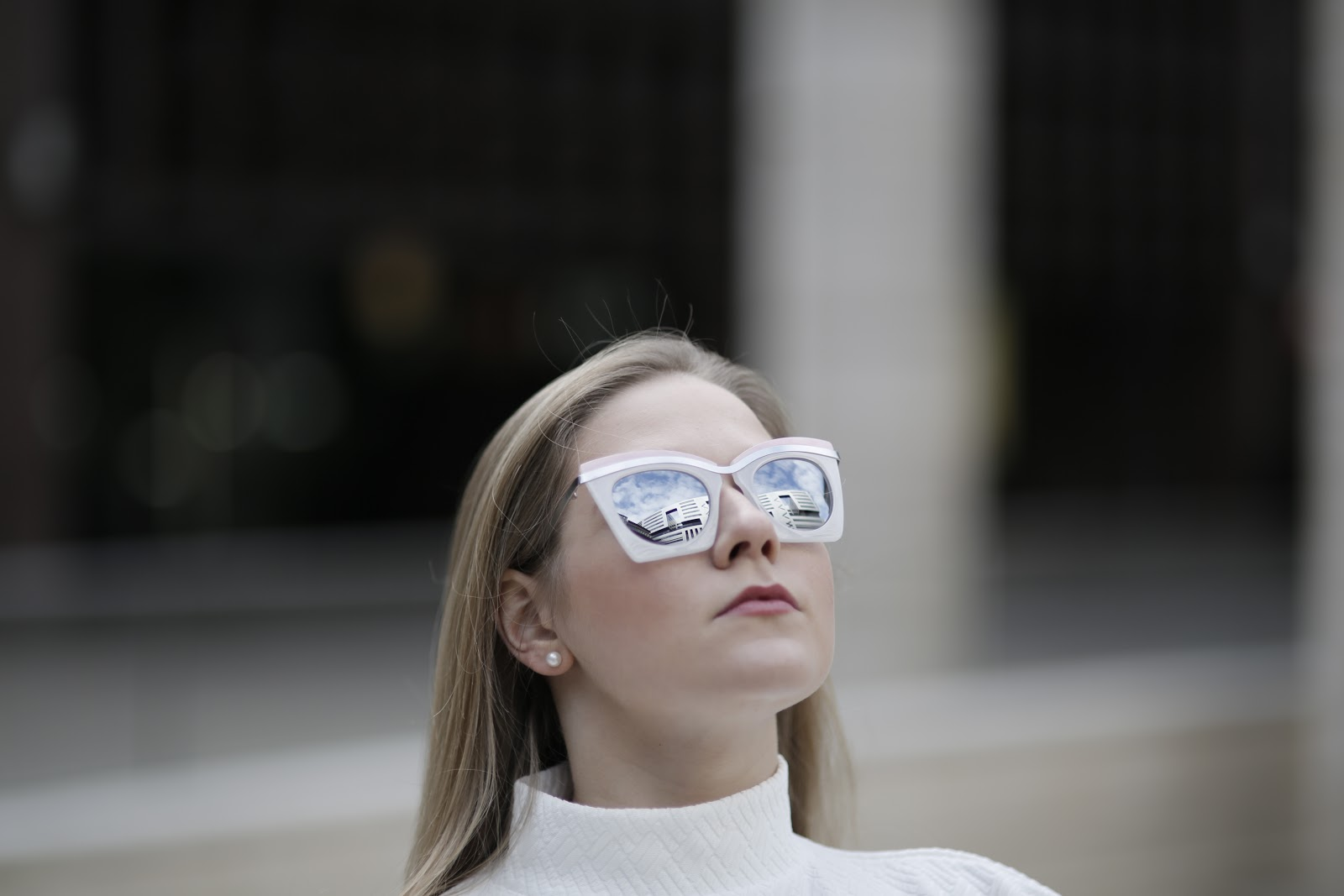 Girl wearing retro sunglasses with reflection of the sky in the lenses