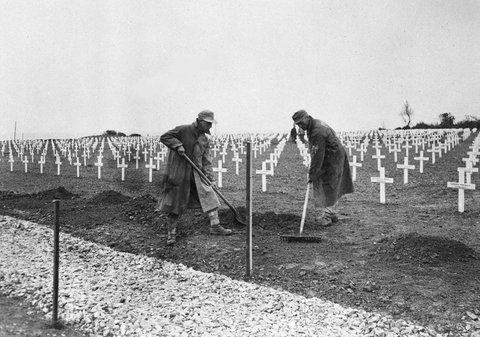 One year after the D-Day landings in Normandy, German prisoners landscape the first U.S. cemetery at Saint-Laurent-sur-Mer, France, near