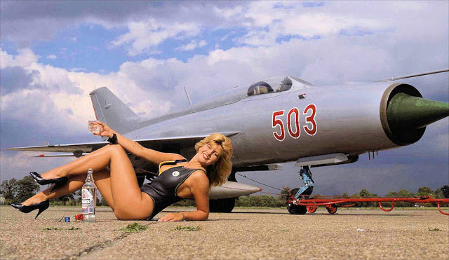 Girl in swimsuit and heels drinks vodka in front os MiG 21 jet