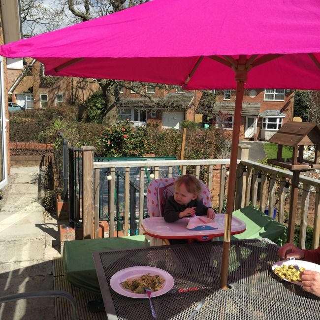 toddler in highchair under sun umbrella