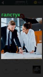 Над столом склонились женщина и мужчина в галстуке, рассматривая чертеж