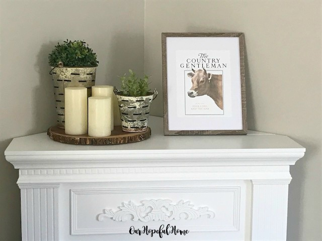 cow art in frame wood slice riser LED candles olive buckets