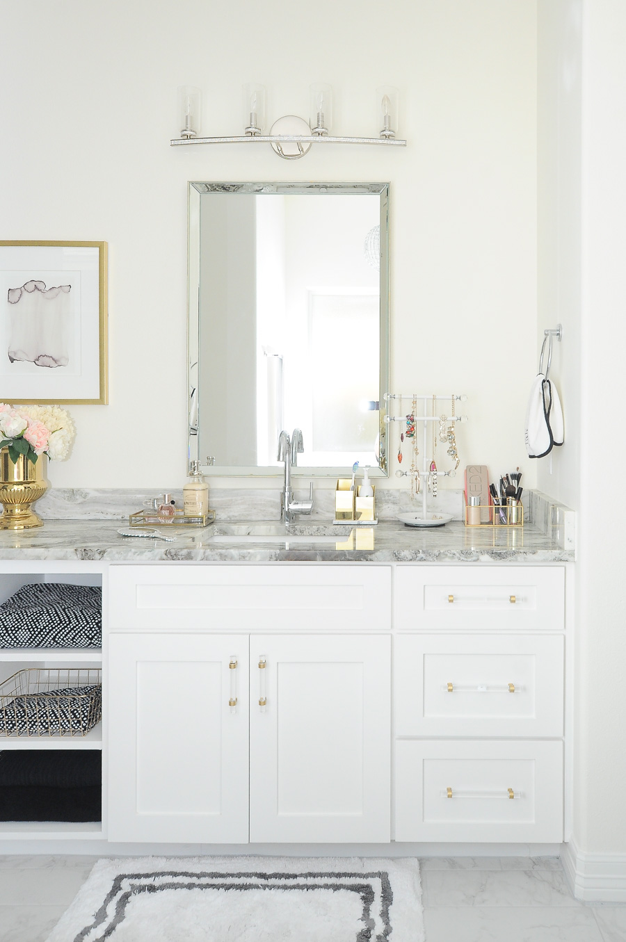 Beautiful white shaker cabinets with brass and gold lucite pulls styled to perfection in this bright white and gold master bathroom. I love the open shelving for towels and the gorgeous mirror and crystal lighting!