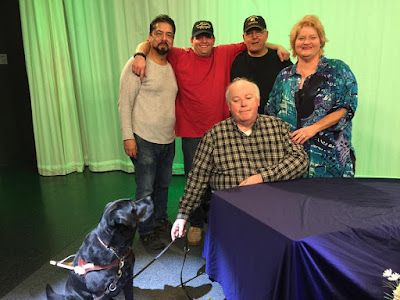 The crew take a break for a photo on the set of Blindside Fresno. Standing at back, Left to Right Rene Gomez, 'Ace Manelski, Steve Manelski and Darcie Elliott: seated and at front Left to right, Guide Dog Leif and William Elliott