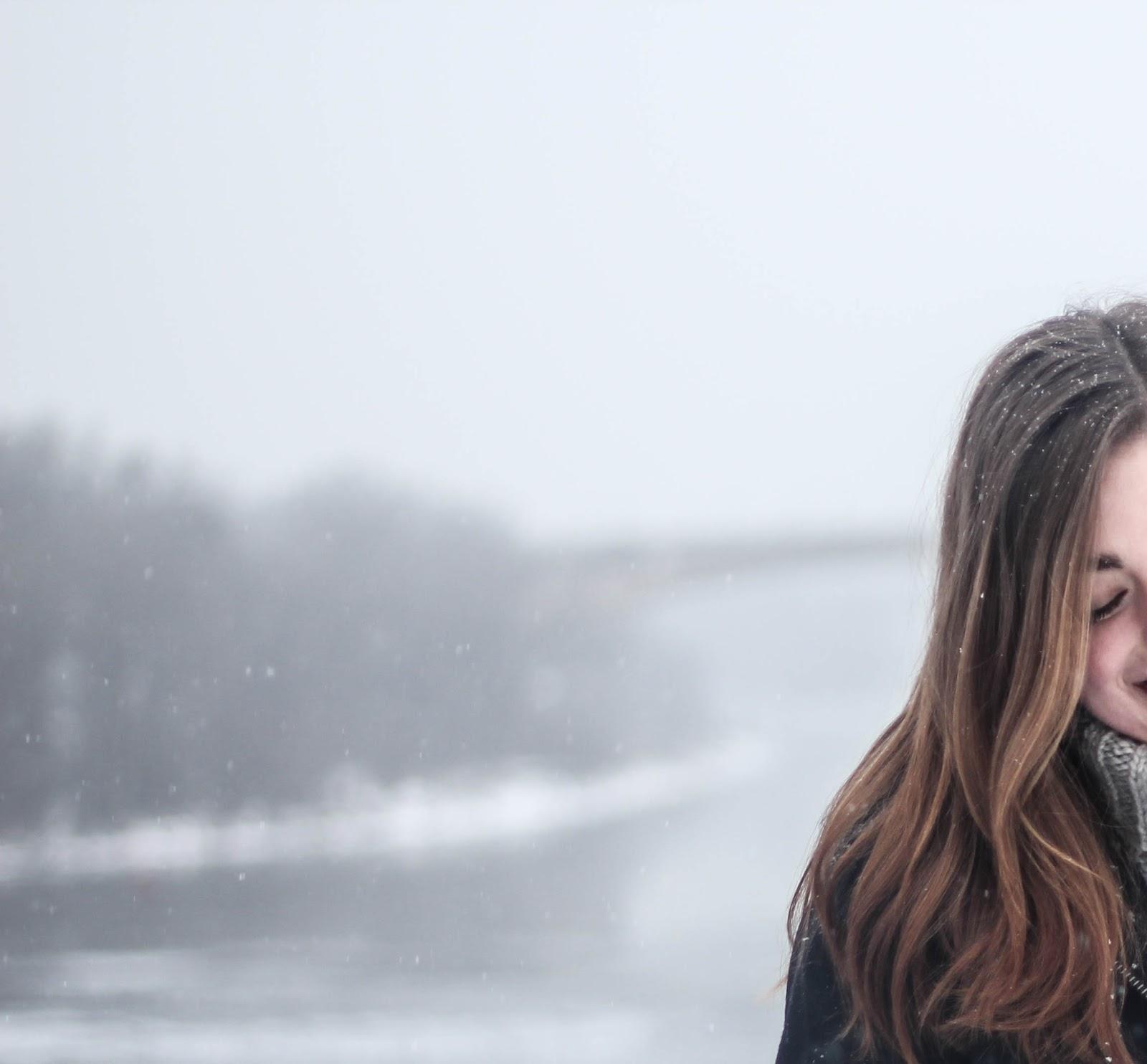小雪の中に微笑んで俯く女性