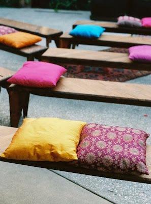 Montaje para ceremonia con bancos de madera y cojines étnicos. Organización bodas Cádiz. Wedding planner Cádiz