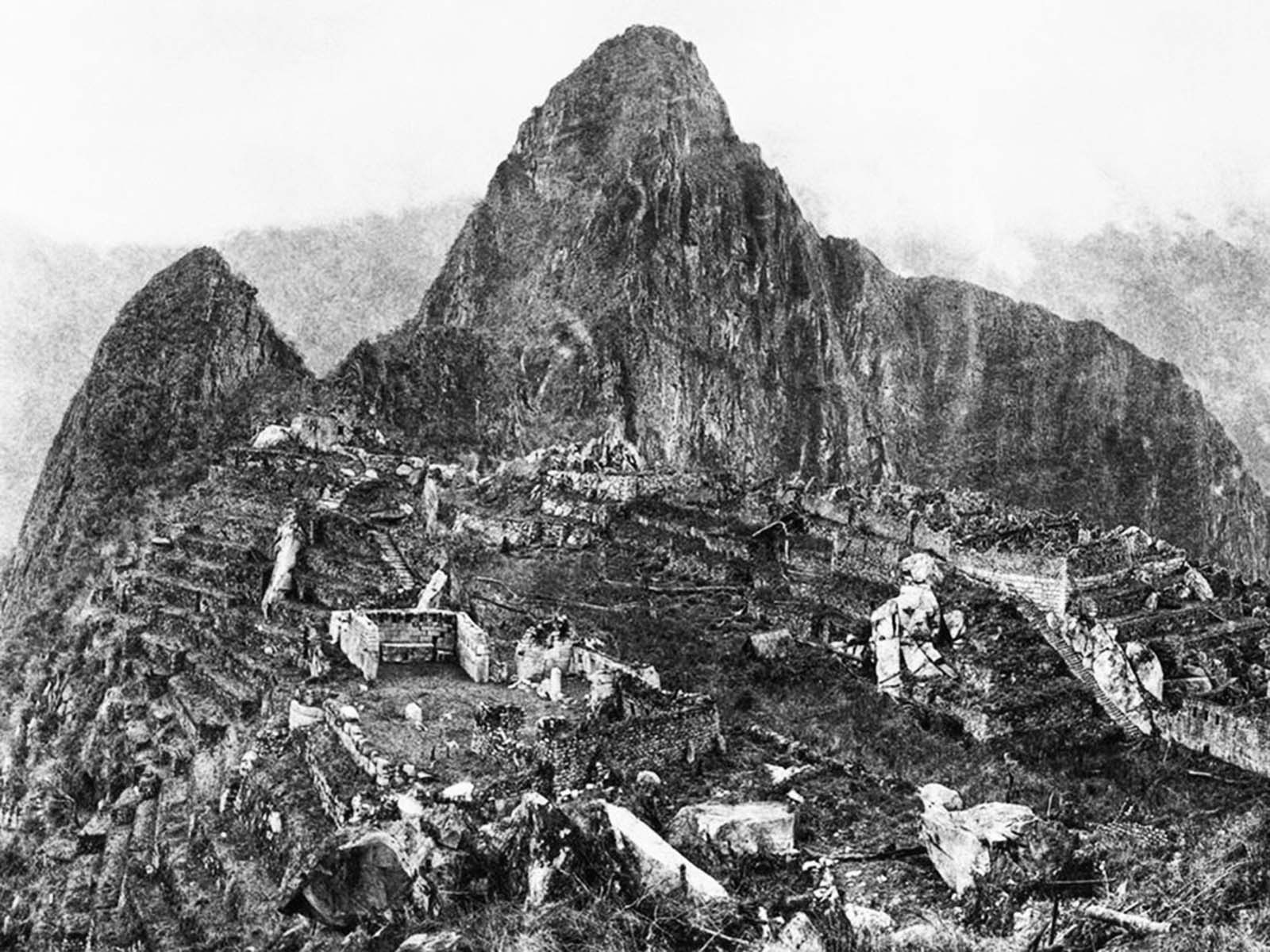 The ruins of Machu Picchu covered in jungle growth in this 1911 photograph taken when Yale archaeologist Hiram Bingham first came to the site.