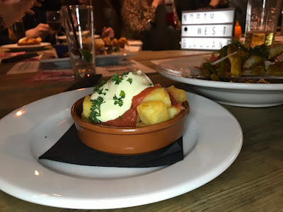 patatas bravas with more food and drinks in the background