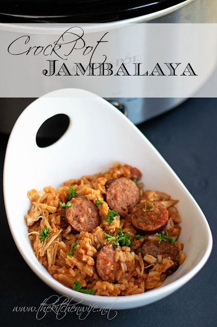 A bowl of crockpot jambalaya in a white bowl, sitting by the crockpot.