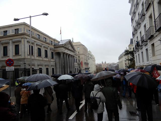 manifestantes bajo paraguas se dirigen al congreso