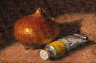 Oil painting of a brown onion beside a yellow tube of artists' oil paint..
