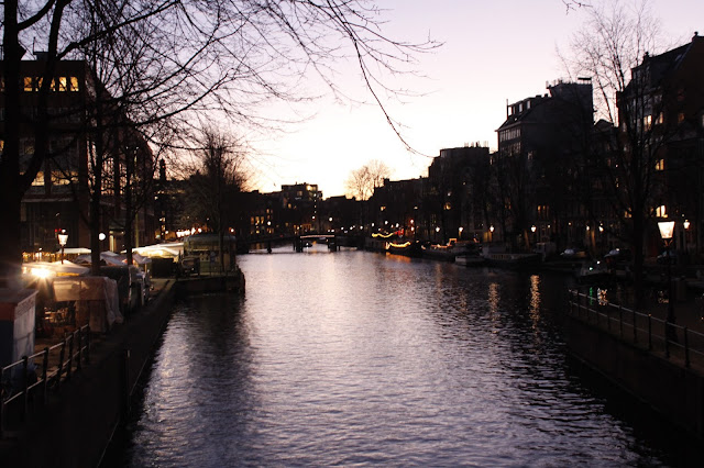 An image of an Amsterdam canal in the evening with fairy lights and reflections.