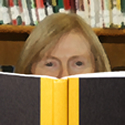 Woman looking over the top of a book