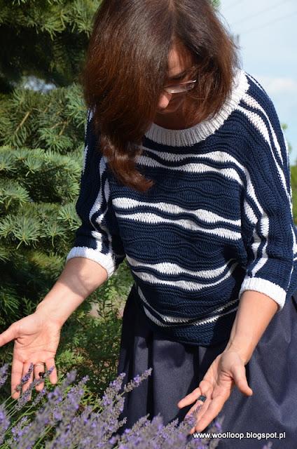 Pochylona postać w dzianinowym sweterku w marynarkim stylu