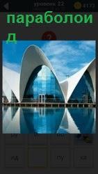 На берегу водоема стоят три здания параболоидной форме, отражаясь в синей прозрачной воде