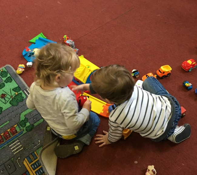 two toddlers playing, one snatching car from another