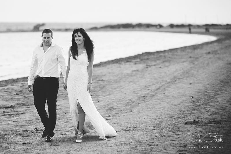 pareja de novios caminando por la arena