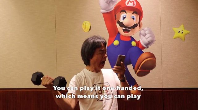Shigeru Miyamoto working out barbell playing Super Mario Run weight lifting exercise one hand