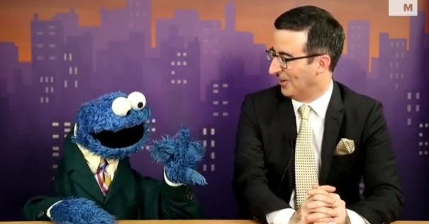 Cookie Monster and John Oliver at news desk in suits