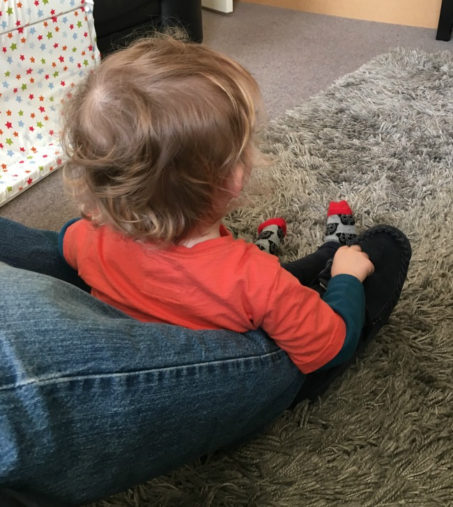 Planting, Postman Pat and a Picnic Toddler sat at feet of adult watching TV