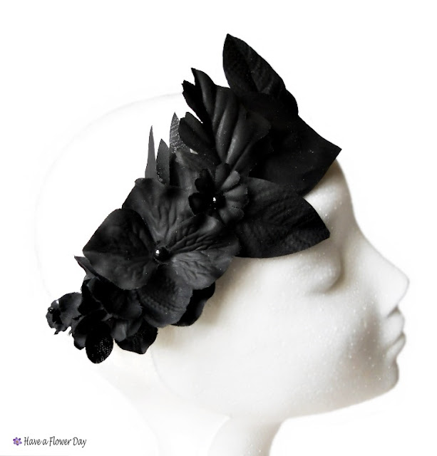 Corona negra con hojas y flores · Black crown with leaves and flowers